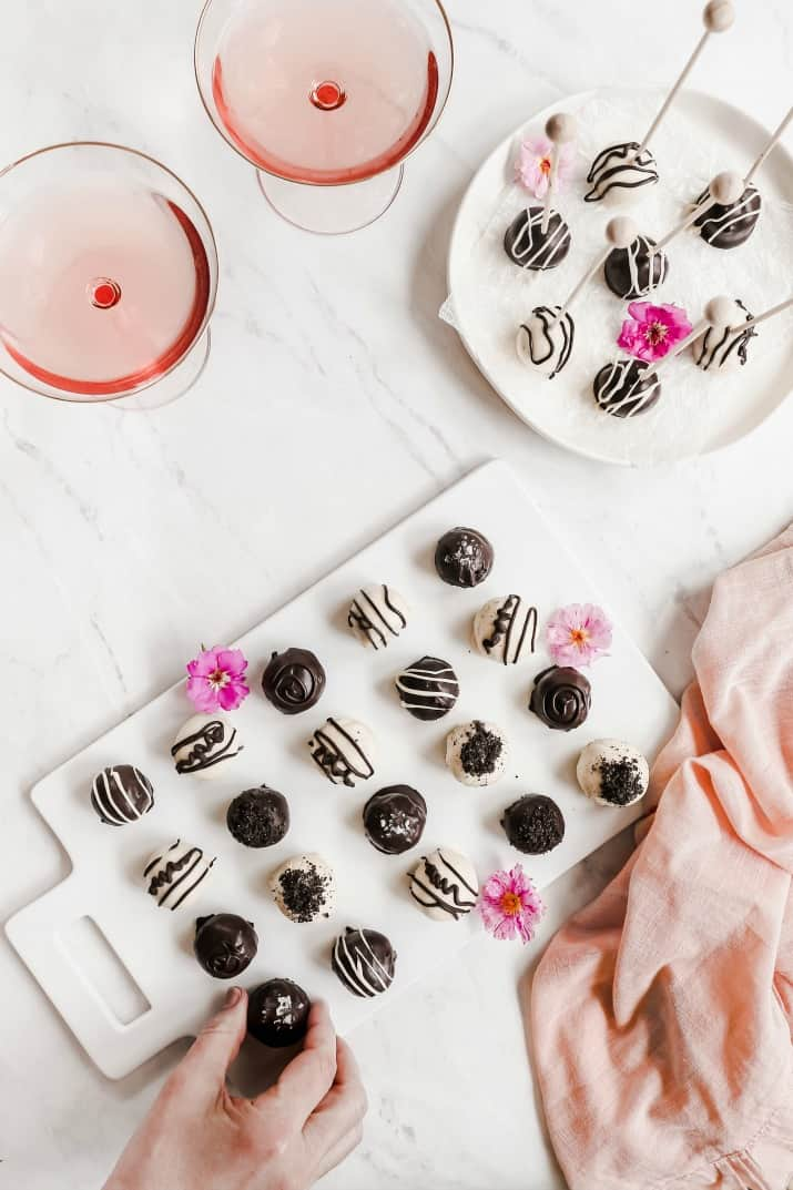 Oreo cookie balls on white platters with flowers and rose