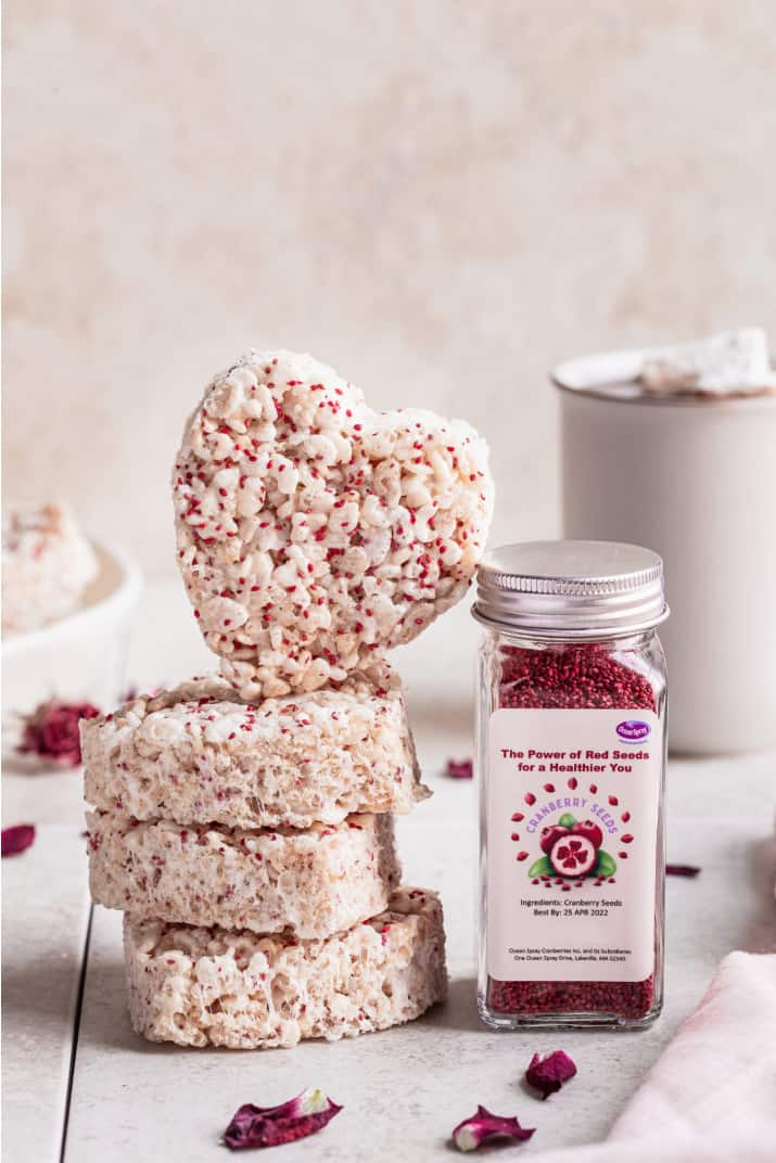 heart shaped krispie treats stacked, next to a jar of cranberry seeds
