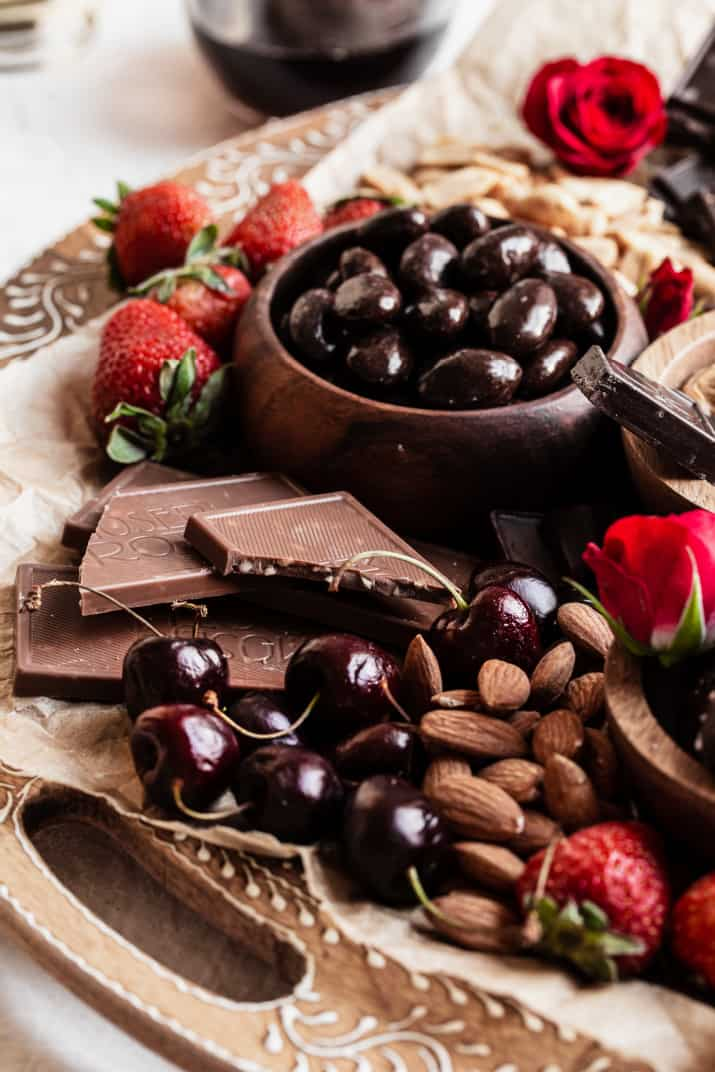 bowl of chocolate covered nuts with cherries, strawberries, and milk chocolate bars.