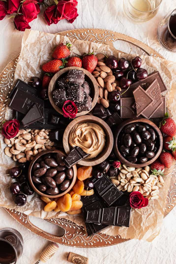 chocolate, nuts, and fruit on round wood platter, overhead