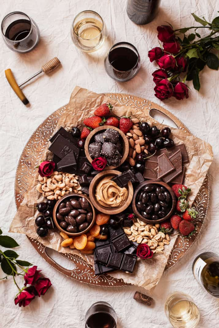 round wood board with chocolate, nuts, fruit, and wine.