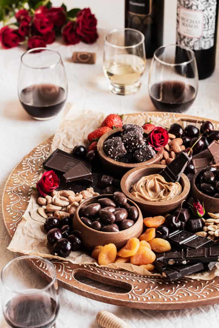 chocolate charcuterie board on tan tablecloth with wine glasses.