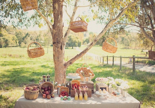 picnic table full of food set under a tree
