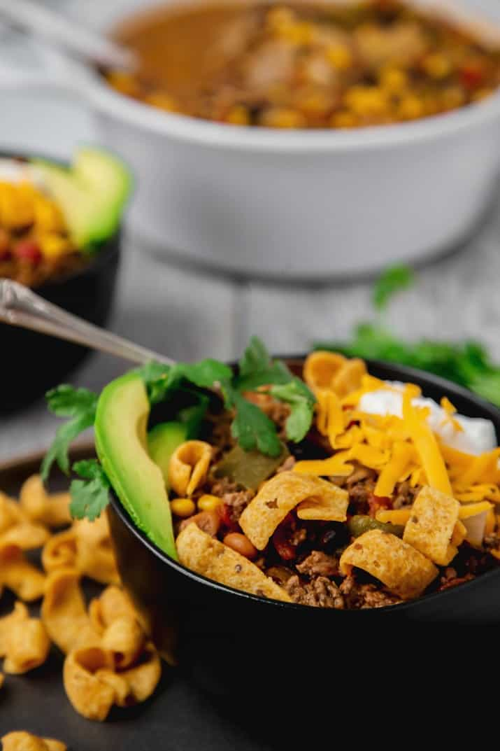 easy slow cooker fiesta chili recipe, close up view topped with corn chips and avocado