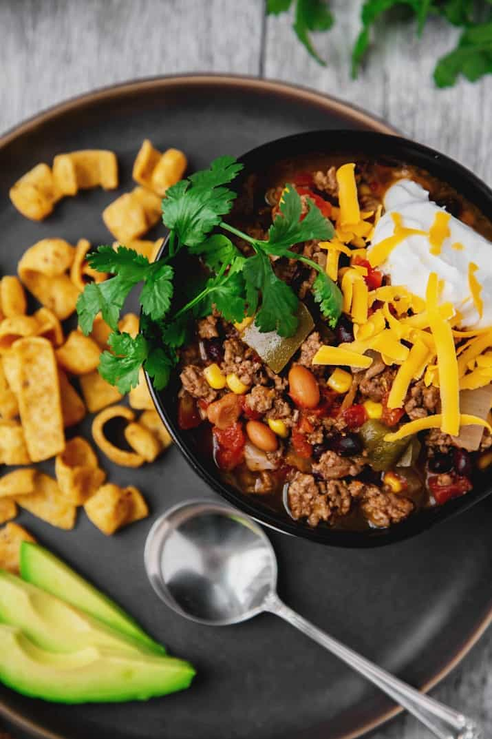 easy slow cooker fiesta chili recipe in black bowl on gray plate, overhead view