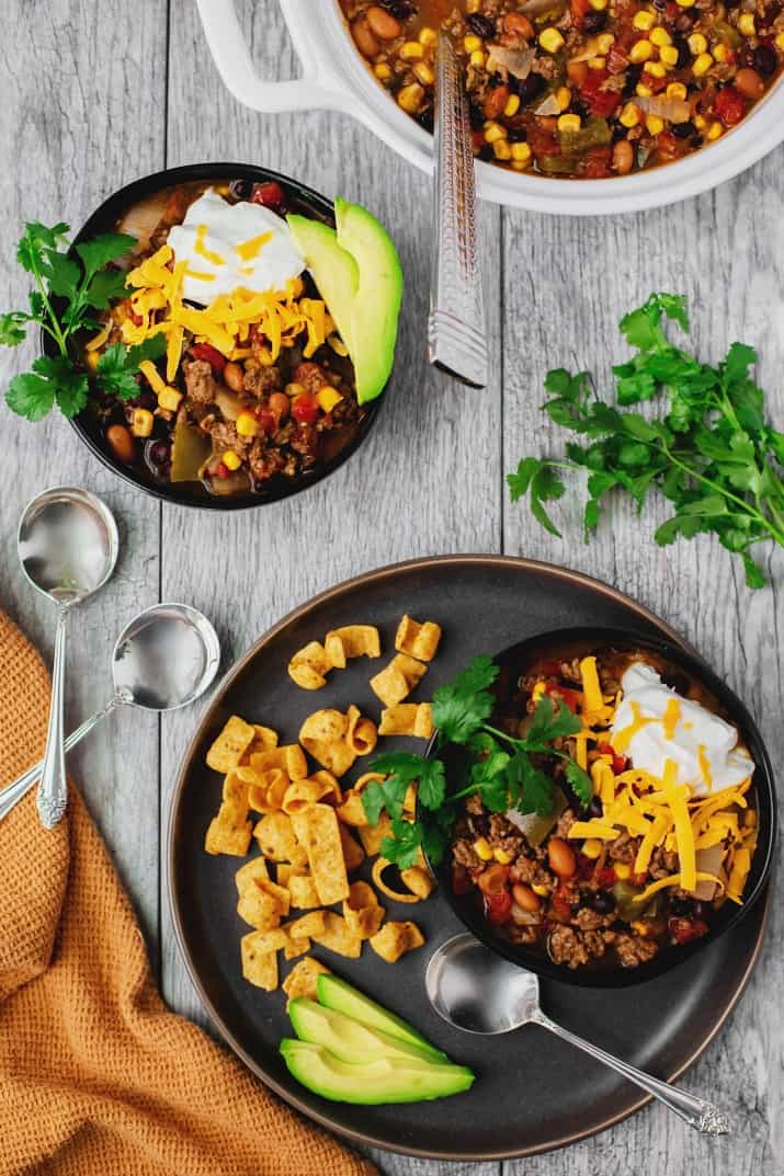 easy slow cooker fiesta chili recipe, overhead view of bowls and large pot