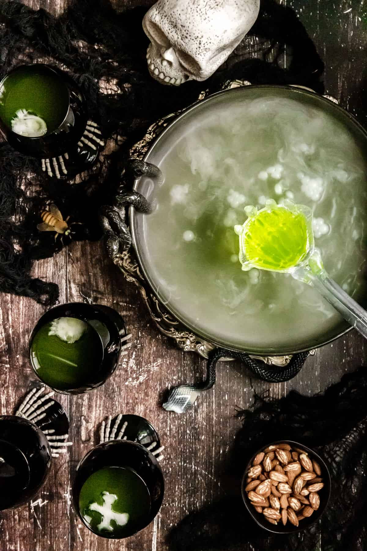 Halloween punch bowl scene with green punch, dry ice, glasses, skull, on wood table