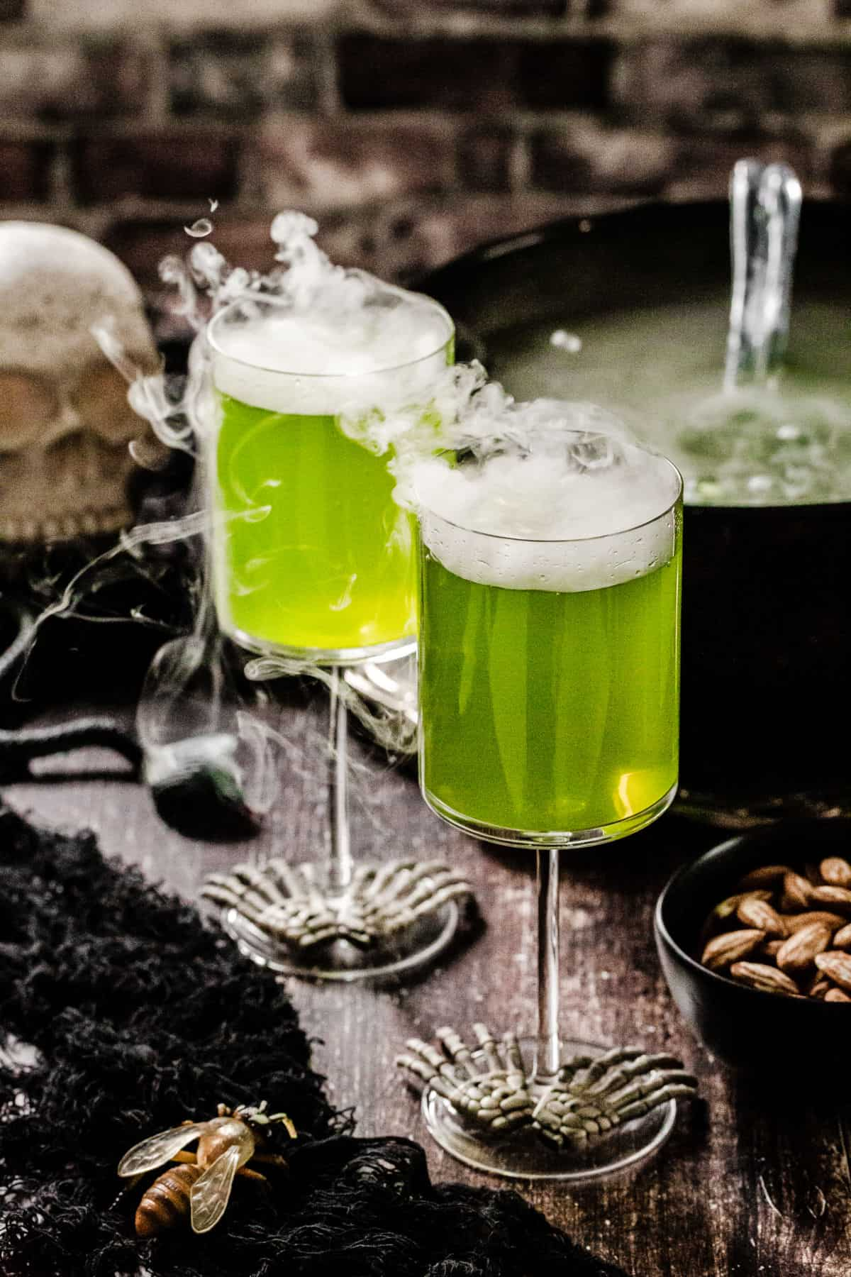 two wine glasses with green drink and dry ice fog