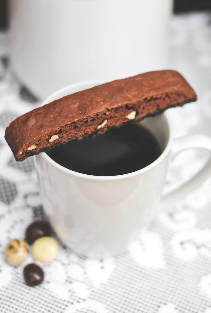 mug of coffee with chocolate biscotti on top