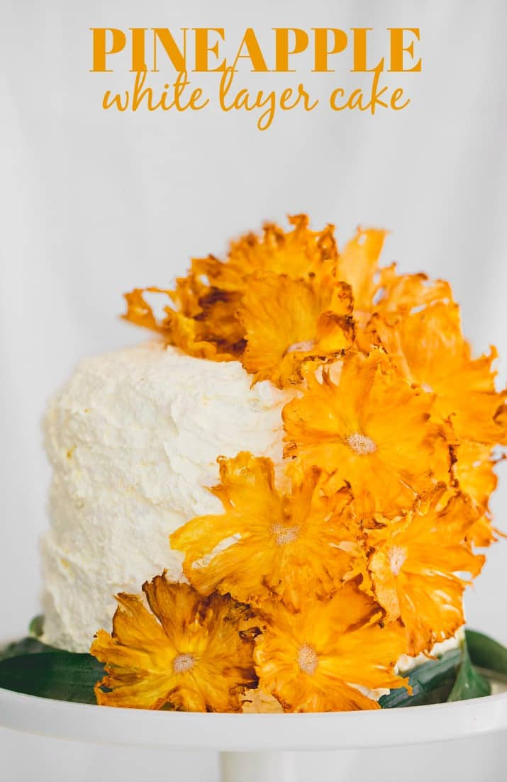 pineapple white layer cake topped with pineapple flowers and text