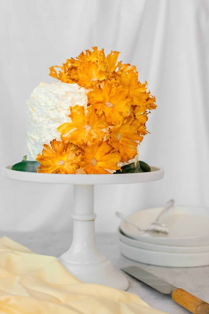 pineapple white layer cake topped with dried pineapple flowers