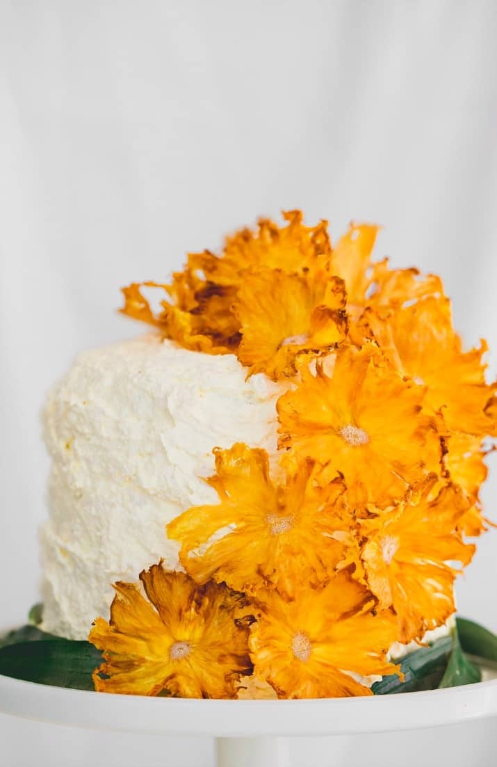 pineapple white layer cake topped with pineapple flowers