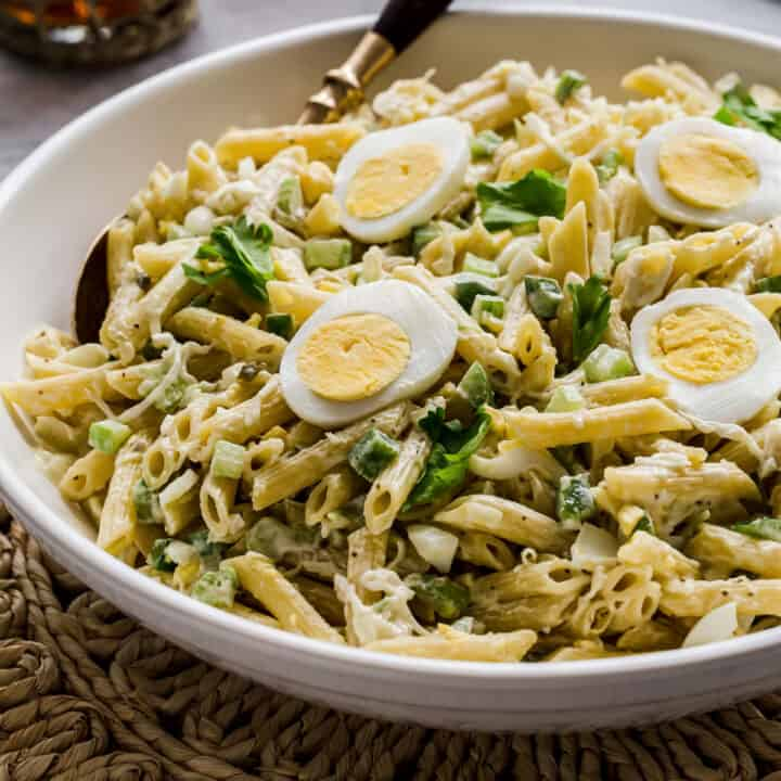 penne pasta salad in white bowl, with sliced egg on top