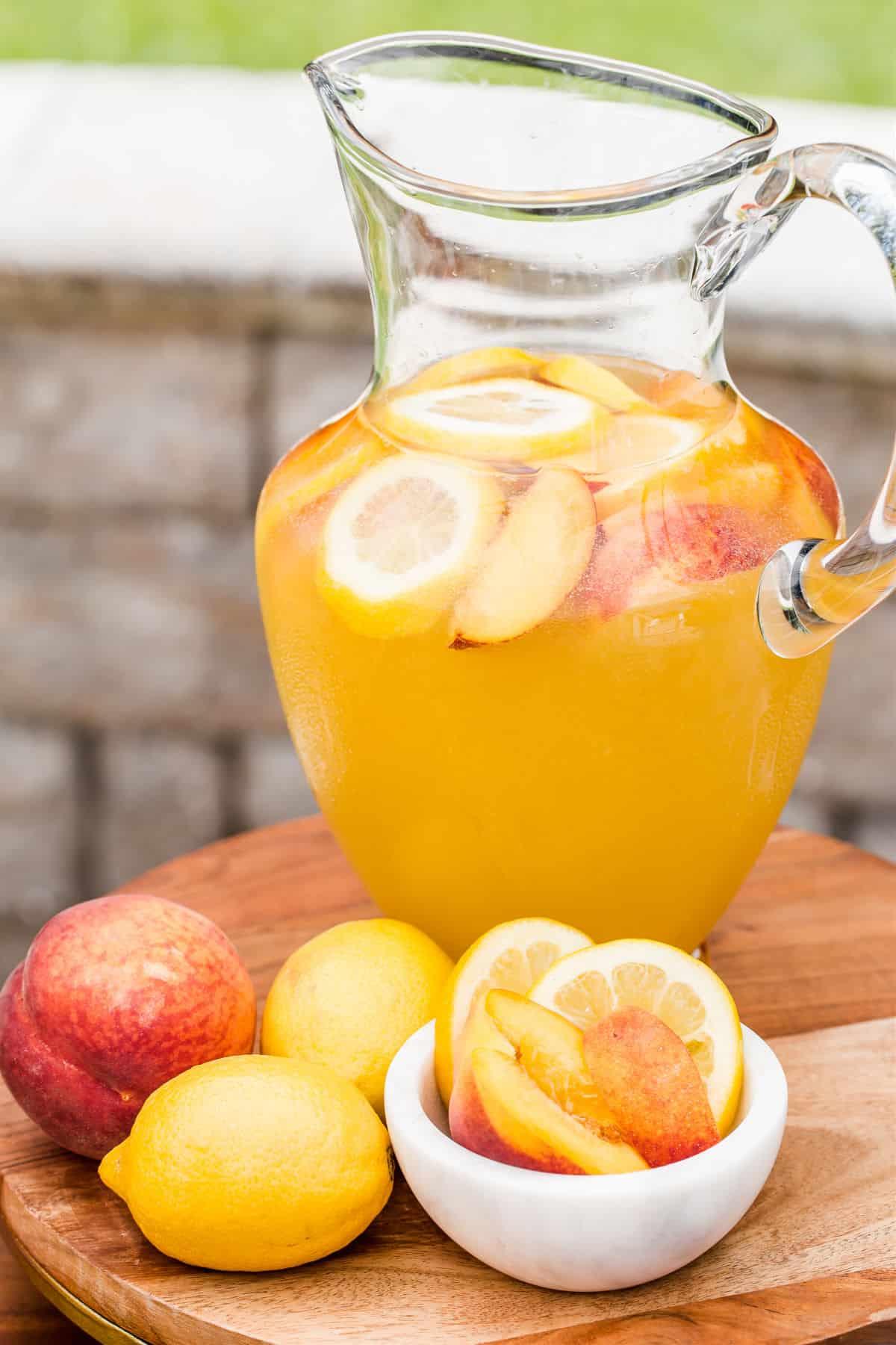 peach lemonade in pitcher with peach and lemons garnish