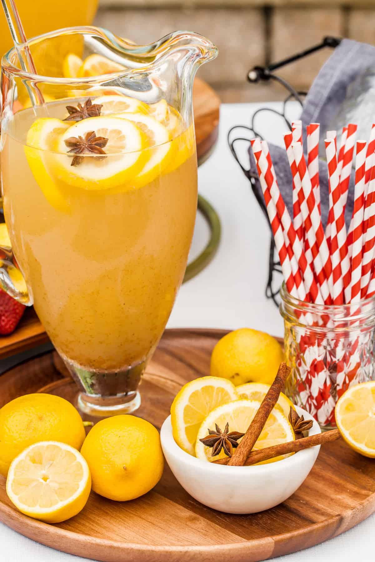 lemonade in pitcher with lemons and cinnamon sticks garnish