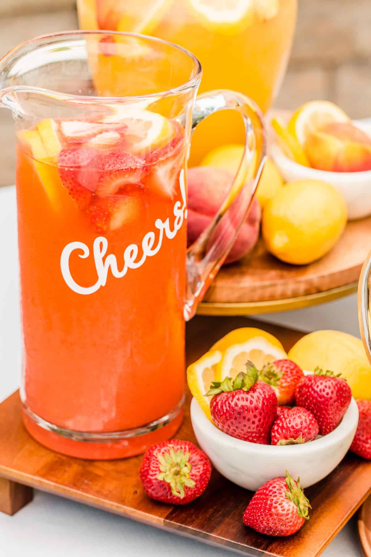 strawberry lemonade in pitcher, surrounded by strawberries and lemons