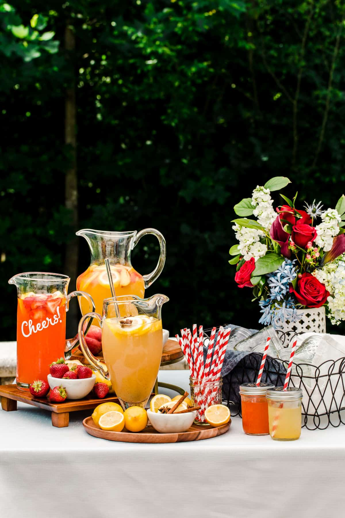 lemonade bar set up outside with 3 pitchers of different flavors, and fruit garnish