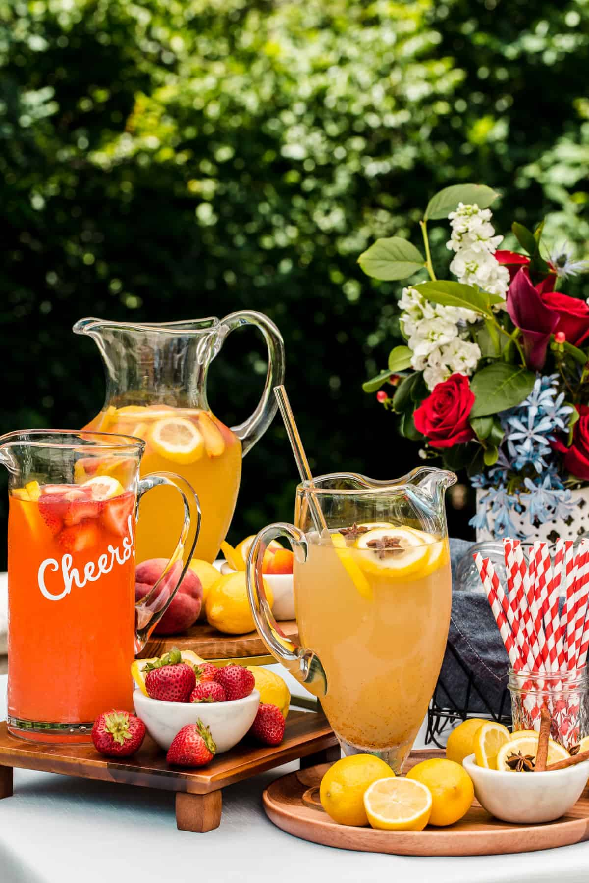 3 pitchers of lemonade in different flavors with fresh lemons and fruit, outside