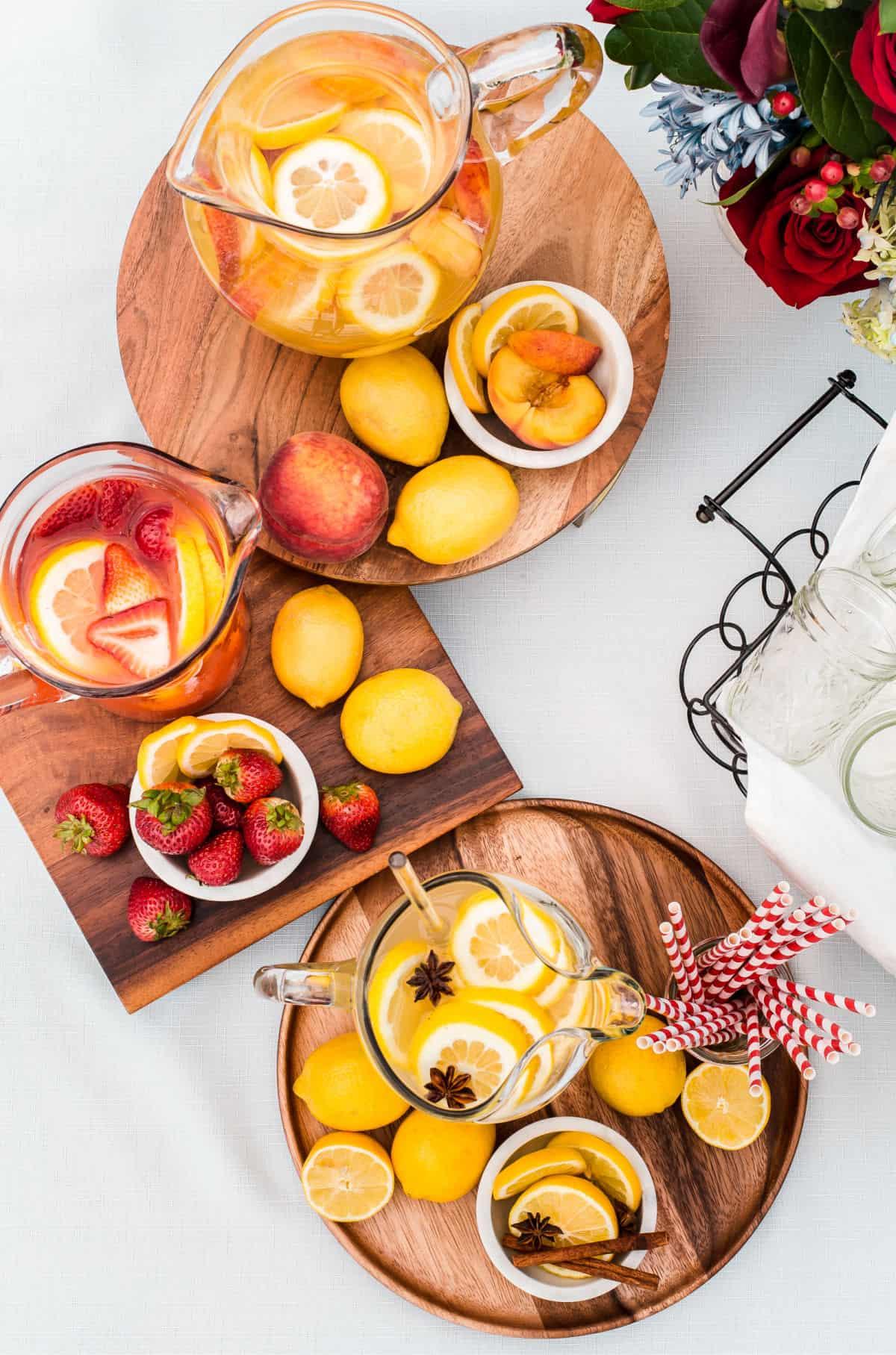 pitchers of lemonade on wood trays, on white table with fresh fruit garnish