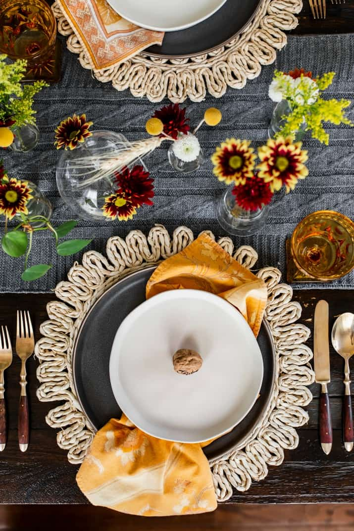 Thanksgiving place setting overhead; gray and white plates with yellow napkin