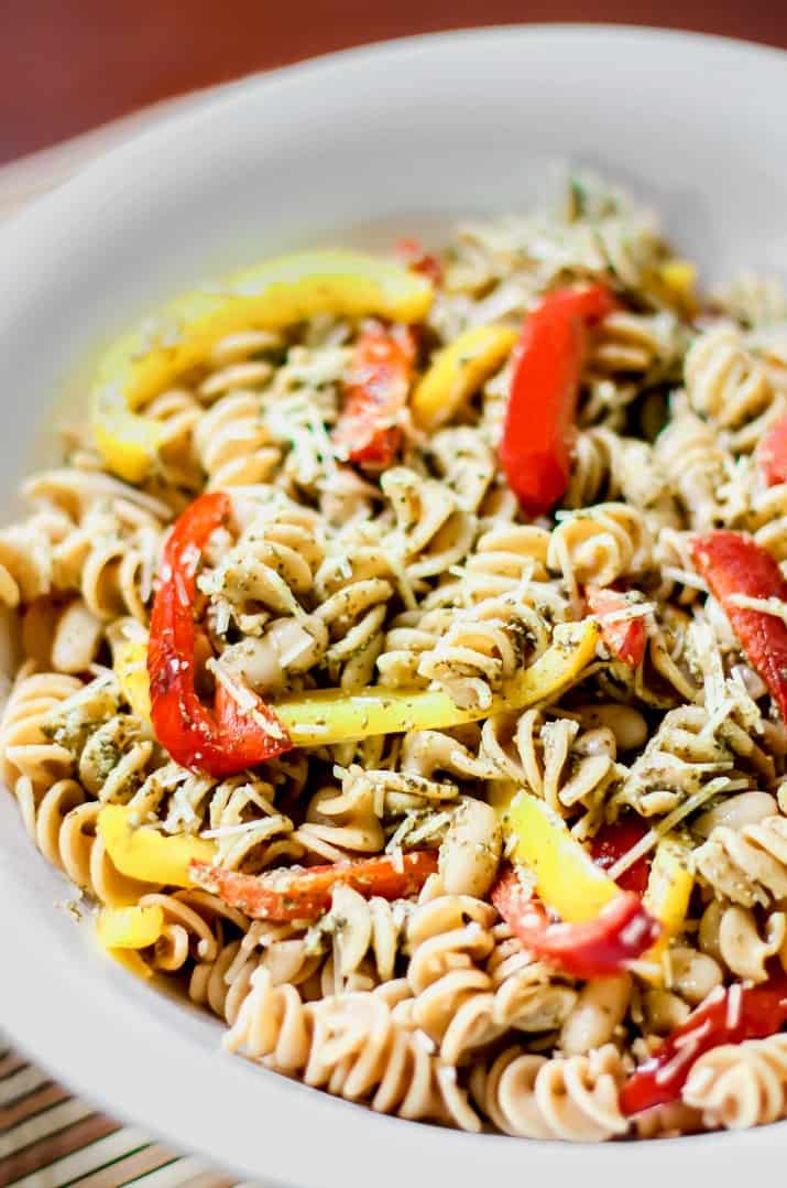 pesto pasta salad with red and yellow peppers in white bowl