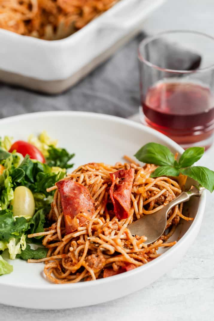white plate of spaghetti and salad