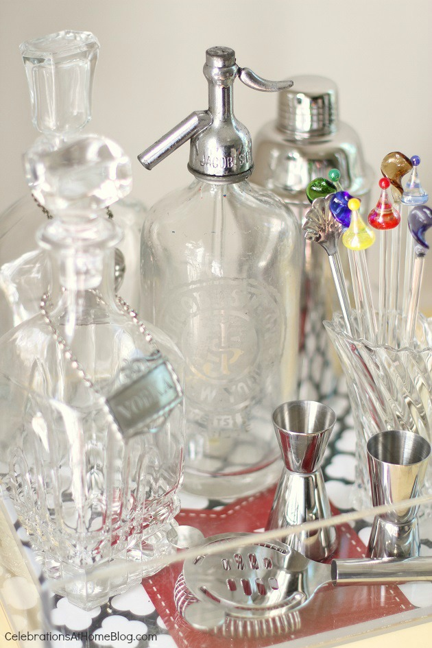 vintage seltzer bottle and decanters on bar cart