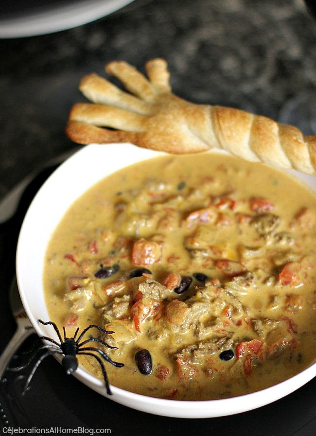 """cheesy chili recipe in white bowl with """"broomstick"""" bread stick"""