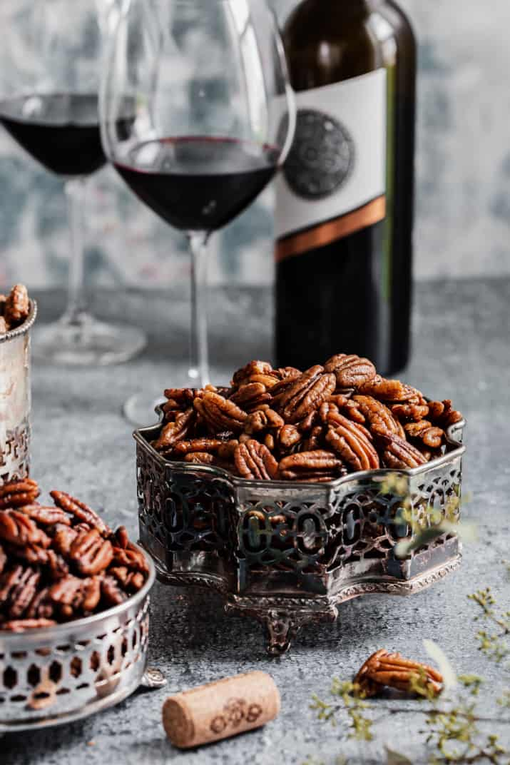 pecans in silver dish on blue table with wine