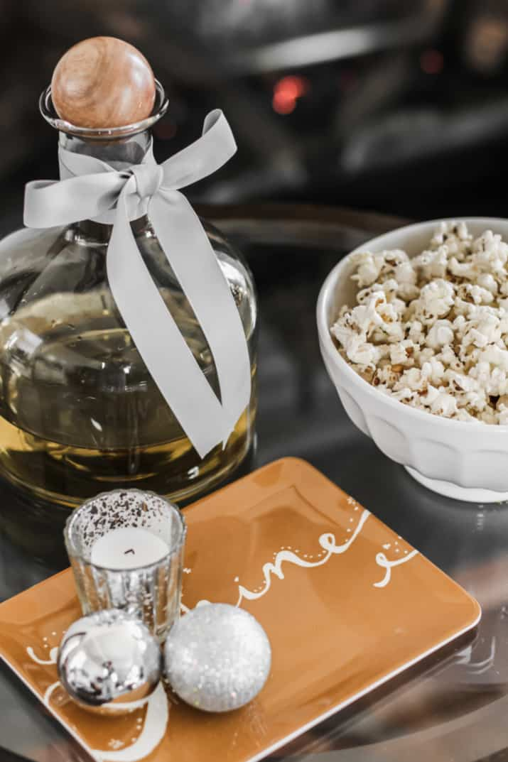 wine decanter, popcorn in a bowl on side table