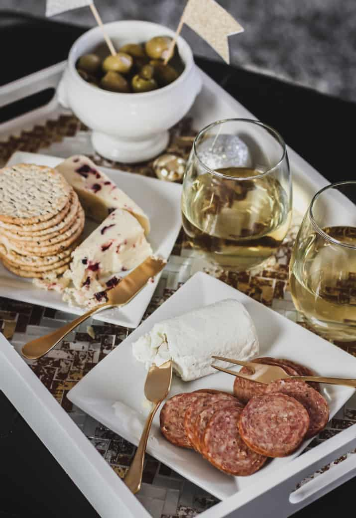white tray with cheese and meats and wine