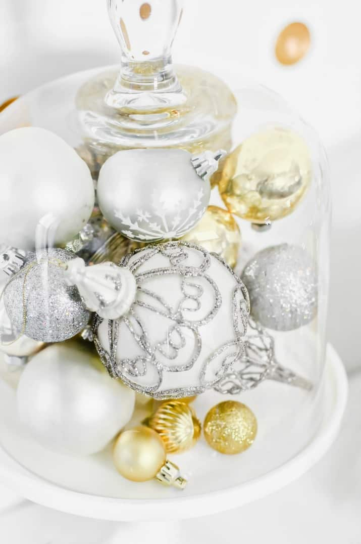 white and gold ornaments under glass cloche