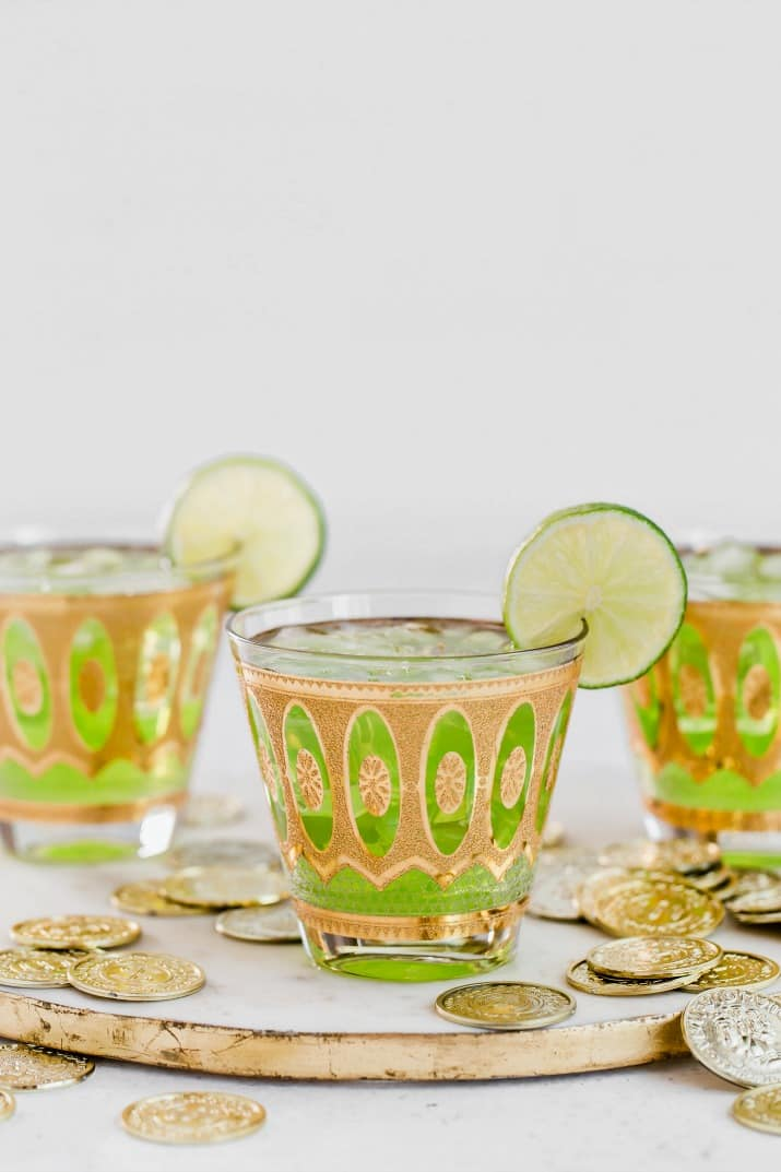 3 green alcoholic drinks on tray with lime garnish