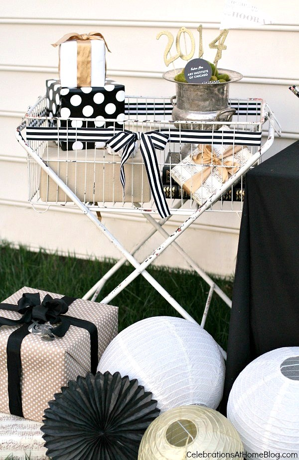 set up a gift receiving area using a large basket and decorative touches like paper lanterns and ribbon