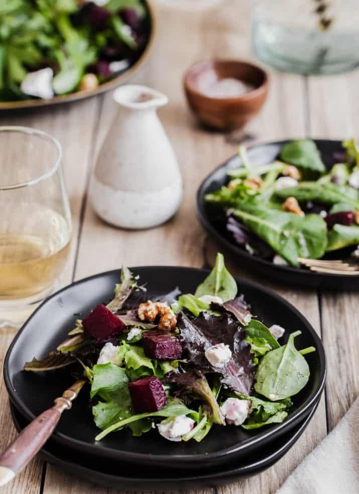 beet green salad on black plates on wood table