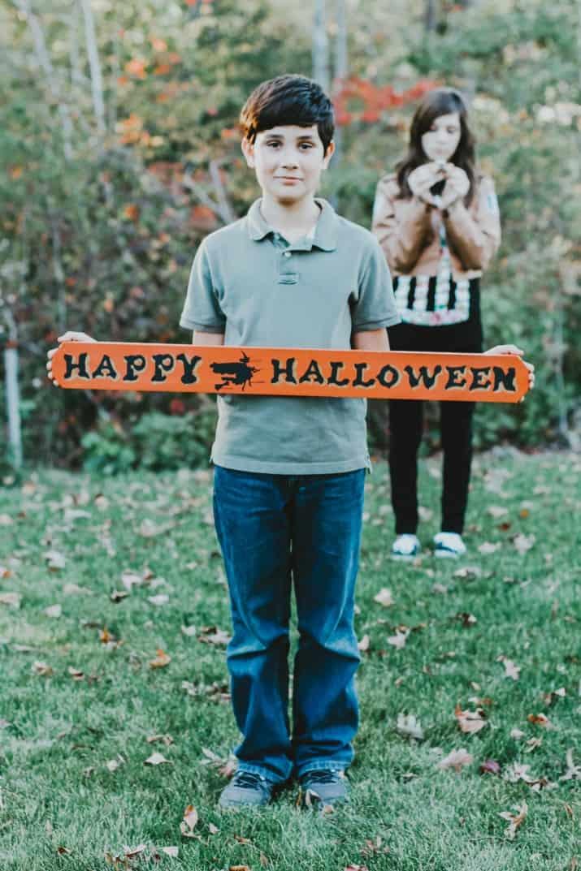 boy holding Happy Halloween sign