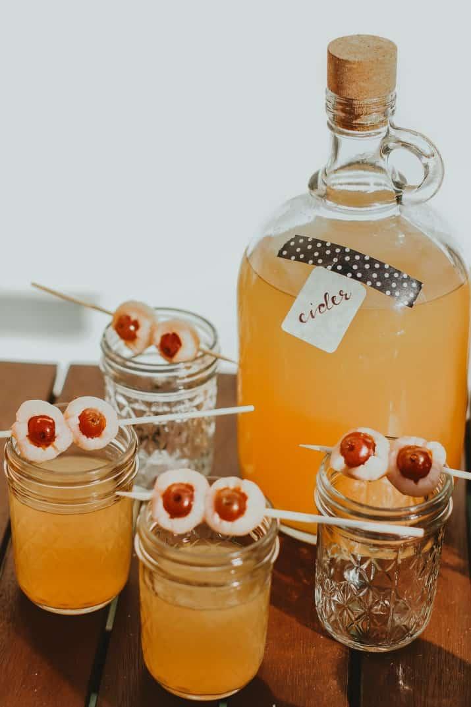 "apple cider in jug with fruit ""eyeballs"""