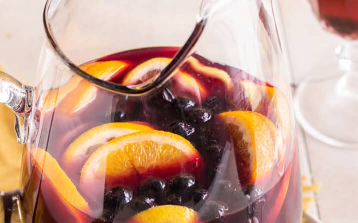 red sangria in glass pitcher with oranges, cherries, and lemons inside