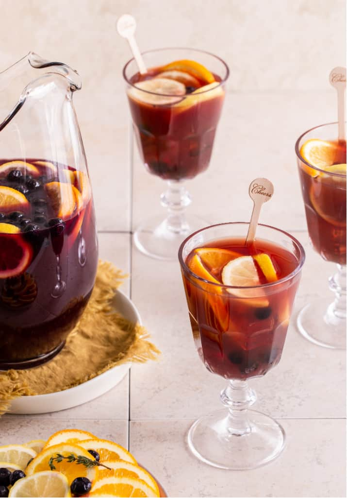 red wine sangria in glass pitcher with 3 glasses filled