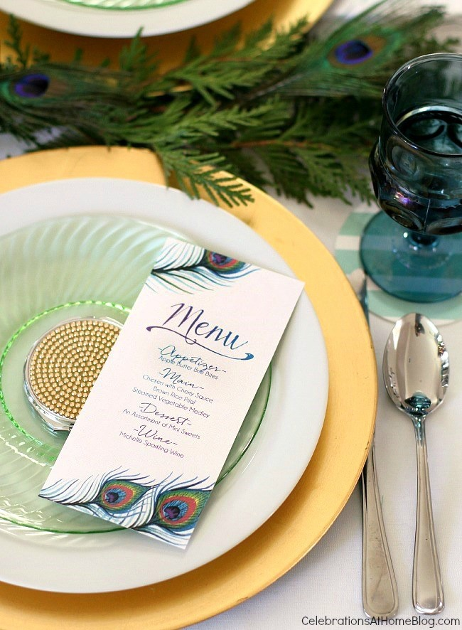 green and gold place setting with peacock themed menu card