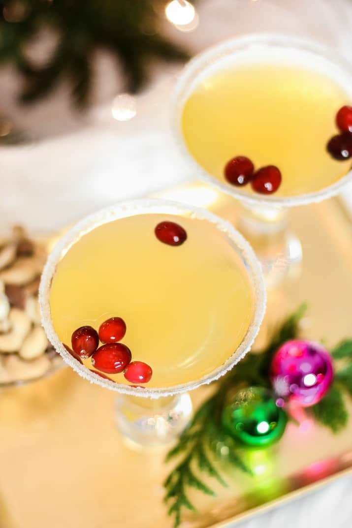 gold colored cocktail with cranberry garnish