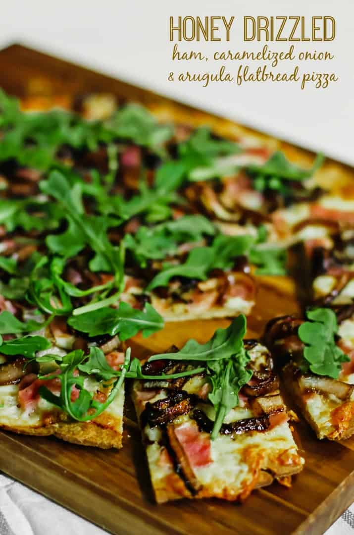honey drizzled ham & arugula flatbread pizza on wood board with text overlay