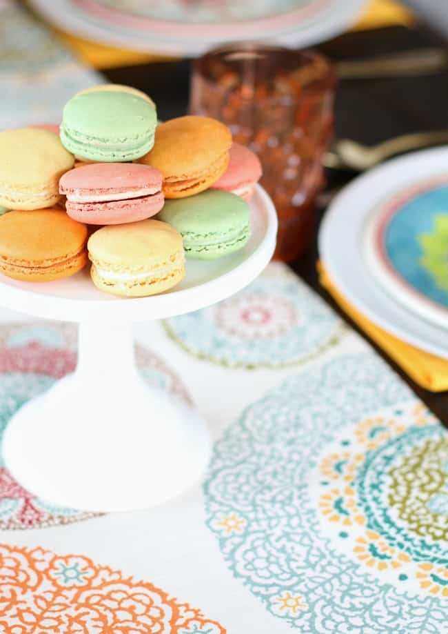 colorful macarons on pedestal; See how to add more color to the dining table with 2 different looks for Spring entertaining. I've set one table, two different ways using the same items. See what I changed, here.