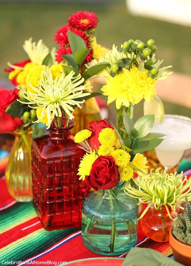 You'll love these entertaining and party ideas for Cinco de Mayo. - centerpiece of mixed flowers in bottles of various colors, sizes, and shapes