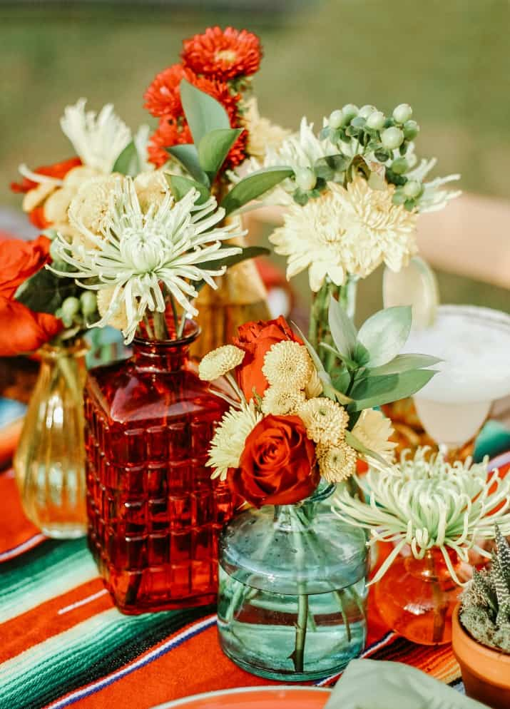 centerpiece of mixed flowers in colorful bottles for cinco de mayo