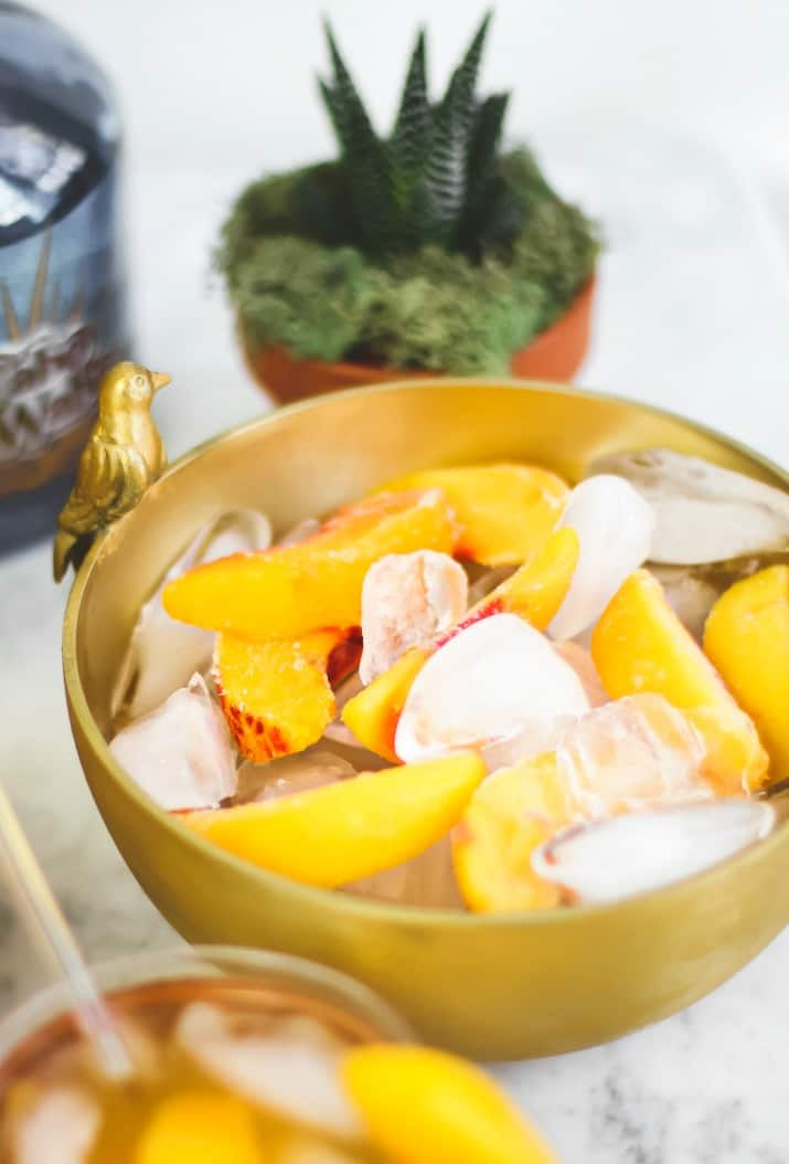 gold bowl filled with peaches on ice