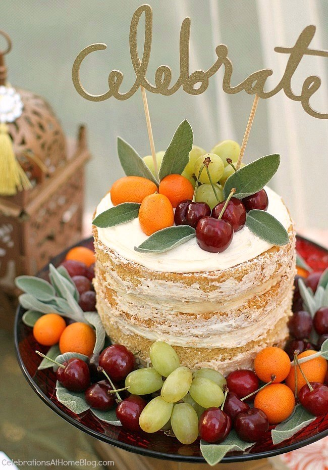 Naked cake decorated with fruit and glitter gold topper. Lots of decor, food, & drink ideas from this Moroccan inspired party.