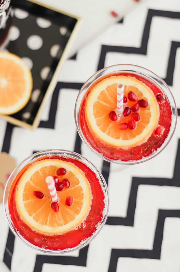 red cocktail with orange garnish on top