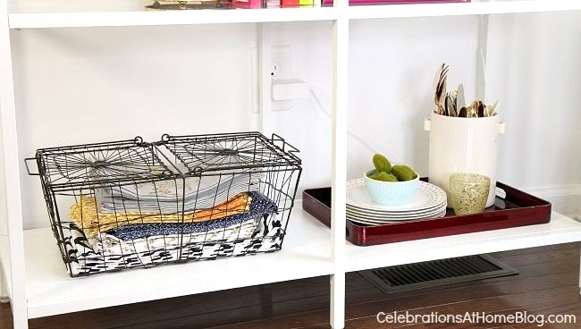 When decorating shelves in the dining room, supplies can be decorative as well as useful when displayed in trays, baskets, and canisters.