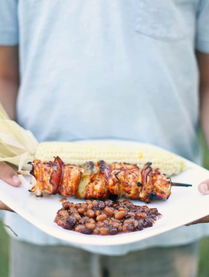 sweet and spicy baked beans with kabobs and corn on white plate